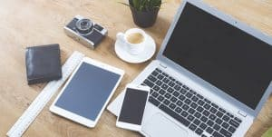Laptop, Ipad, Handy, Portmonee, kamera und eine Tasse Kaffee stehen auf dem Tisch